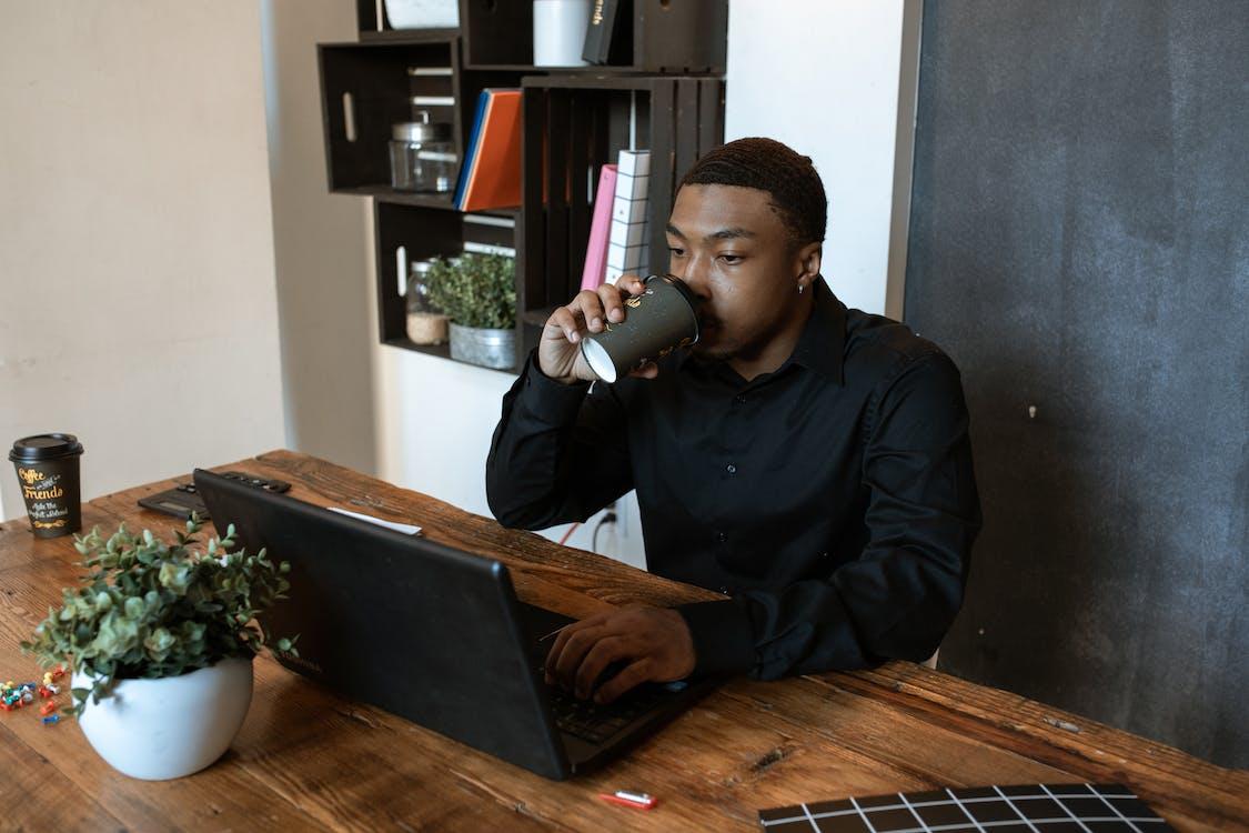 Man in Black Dress Shirt Drinking from White Ceramic Mug