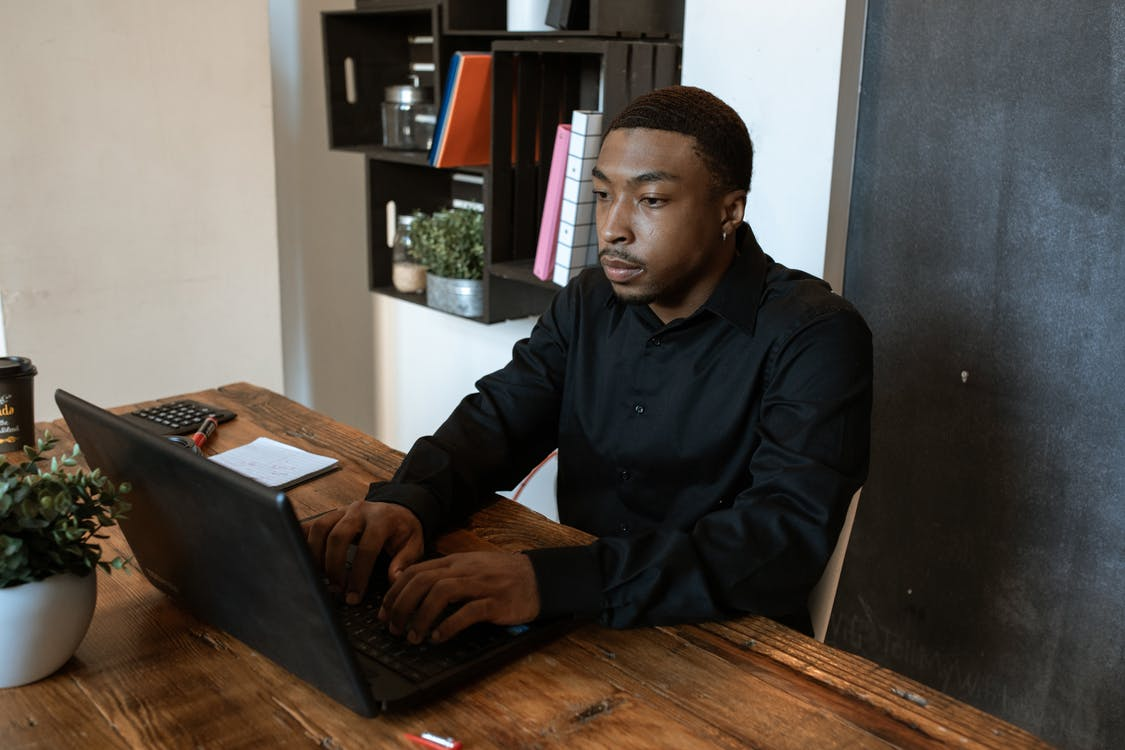 Man in Black Dress Shirt Using Laptop Computer on Brown Wooden Table