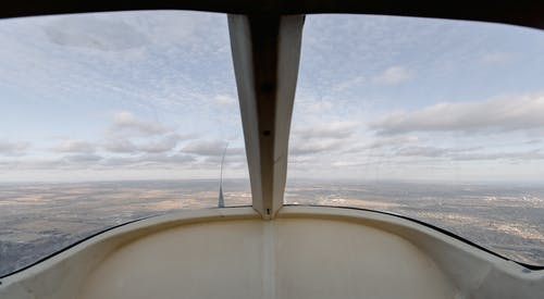 View through windshield of aircraft cockpit soaring over vast plain land under cloudy sky