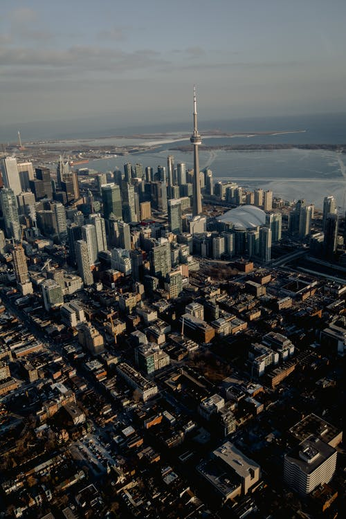 Aerial view of city district with skyscrapers and CN telecommunication Tower on coast of river in Canada
