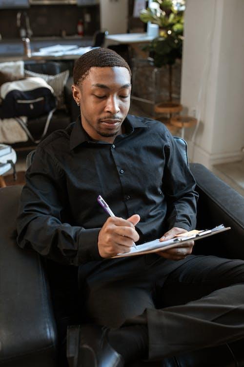 Homme En Chemise Noire à Manches Longues Tenant Un Presse Papiers