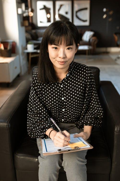 黑色和白色的圓點長袖襯衫,坐在黑色皮革沙發上的女人