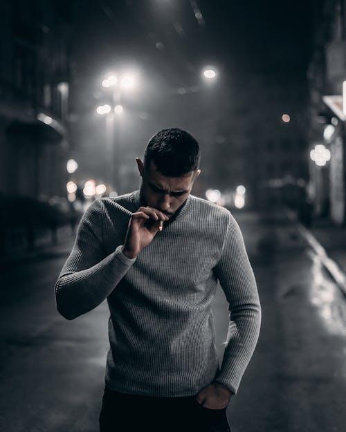 Man in Gray Sweater Smoking Cigarette