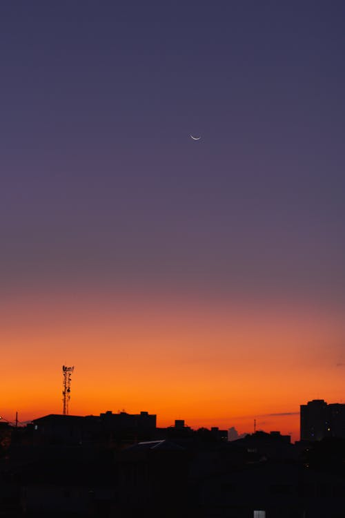 Colorful orange cloudless sky with crescent moon over dark residential buildings located on street in obscure city at sundown time