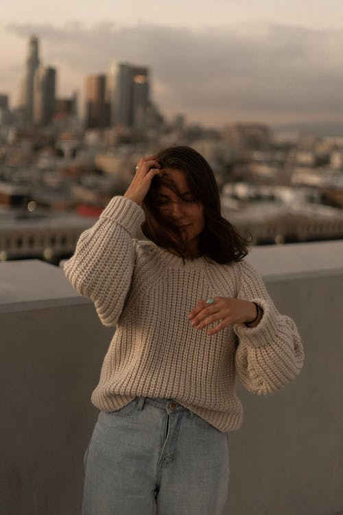 Woman in White Sweater and Blue Denim Jeans Standing on Top of Building