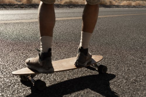 Person in White Socks and Black Nike Sneakers Riding Skateboard