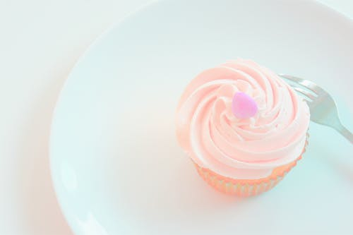 White Icing-covered Cupcake on Plate