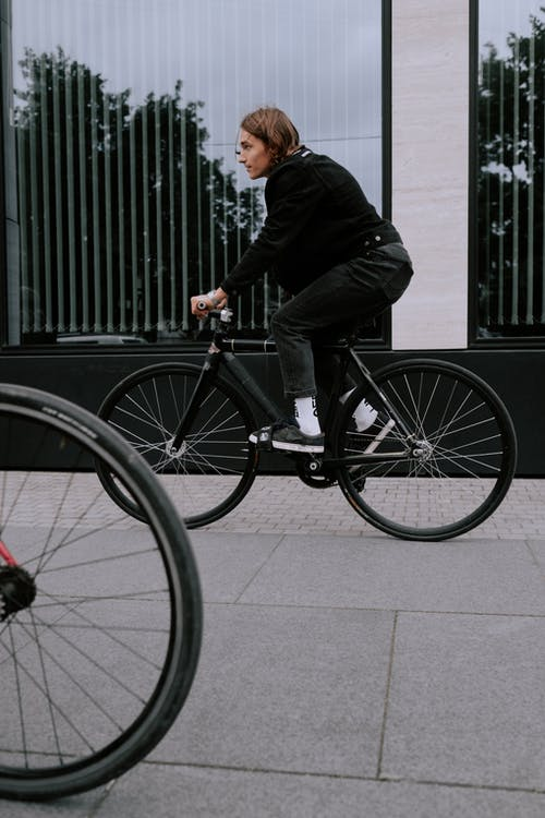 Man in Black Suit Jacket and Pants Riding on Black Bicycle