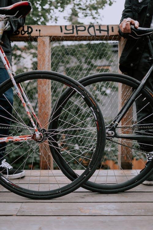 Black Bicycle Wheel Leaning on Brown Metal Fence