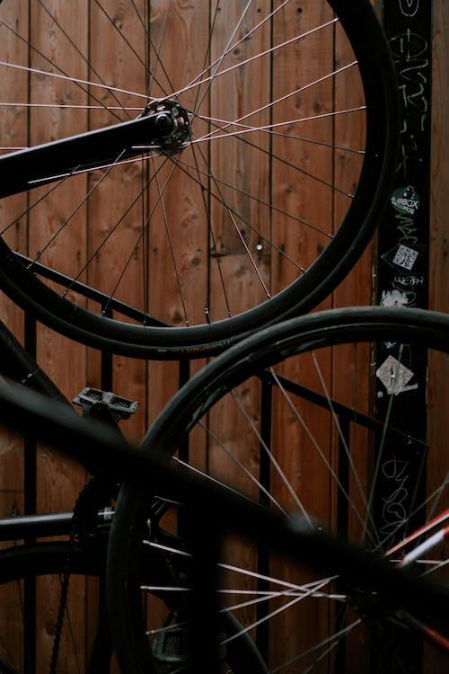 Black Bicycle Wheel on Brown Wooden Floor