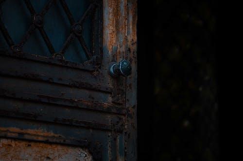 Opened rusty door with metal handle