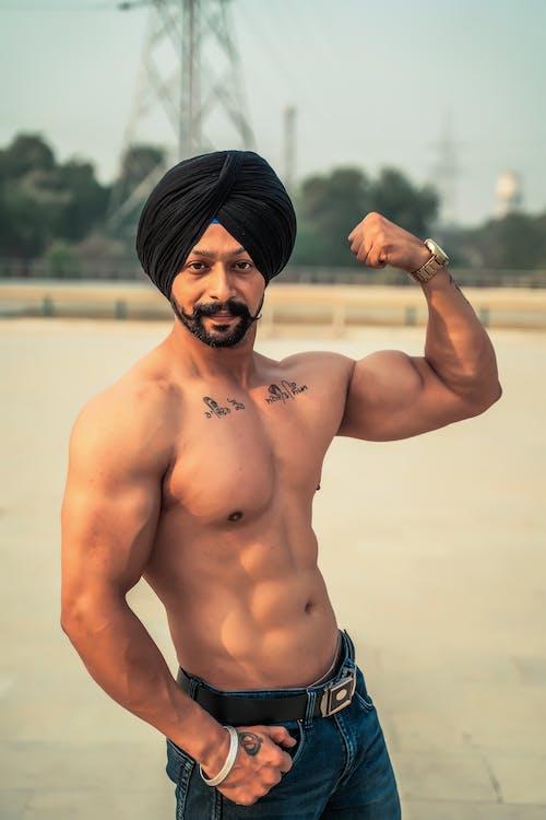 Shirtless Man in Blue Denim Jeans Showing His Biceps