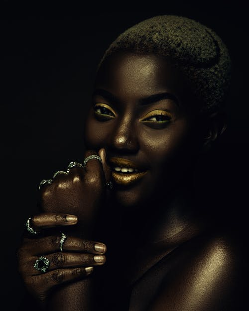 African American female with bright yellow makeup touching face and demonstrating rings while smiling and looking at camera