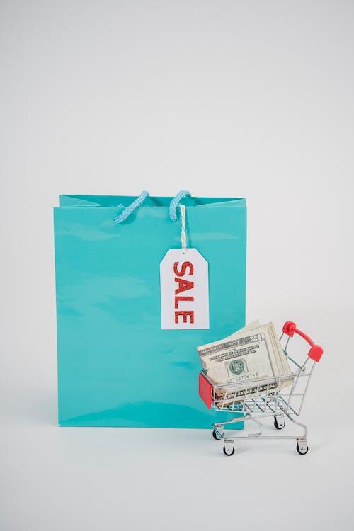 Photo Of Mini Shopping Cart Beside A Shopping Bag