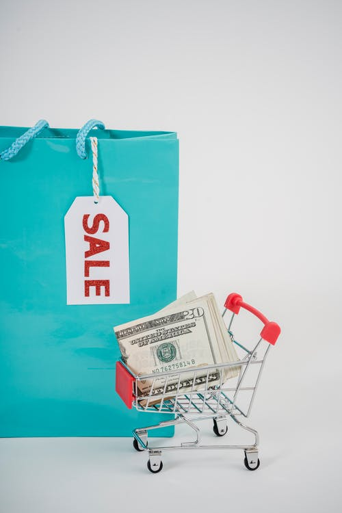Shopping Bag With Sale Card Beside A Mini Push Cart With Dollar Bills