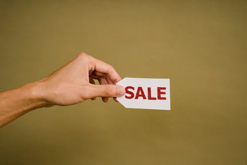 Crop faceless person demonstrating sign Sale