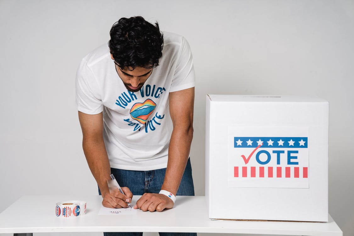 Photo Of Man Writing His Vote On A Paper