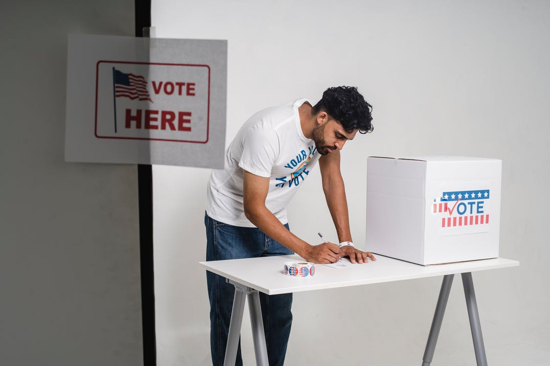 Photo Of Person Writing His Vote On A Paper