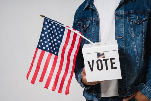 Photo Of Man Holding A Ballot Box With American Flag