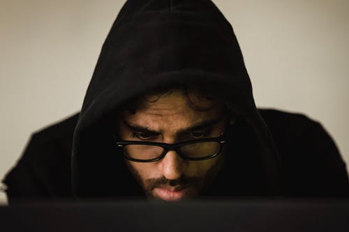 Concentrated hacker in hood using laptop