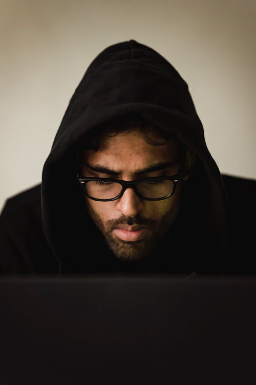 Serious hacker using laptop in studio