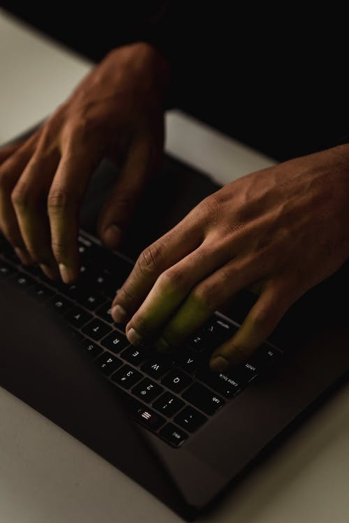 High angle crop anonymous person using netbook and text messaging on keyboard in dark workspace