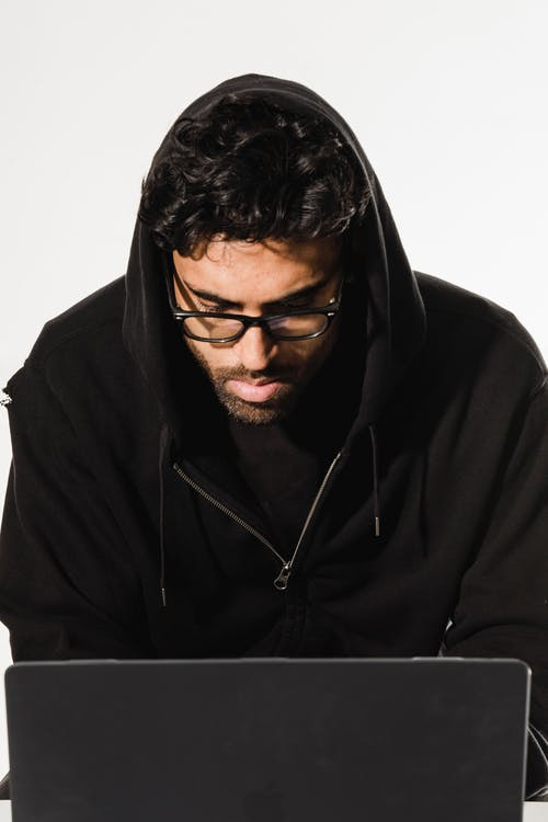 Serious hacker using laptop in workshop