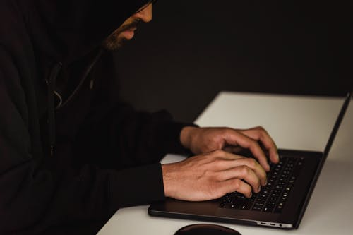 Crop focused programmer hacking database on laptop
