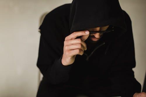 Crop hacker in black hoodie lowering eyeglasses