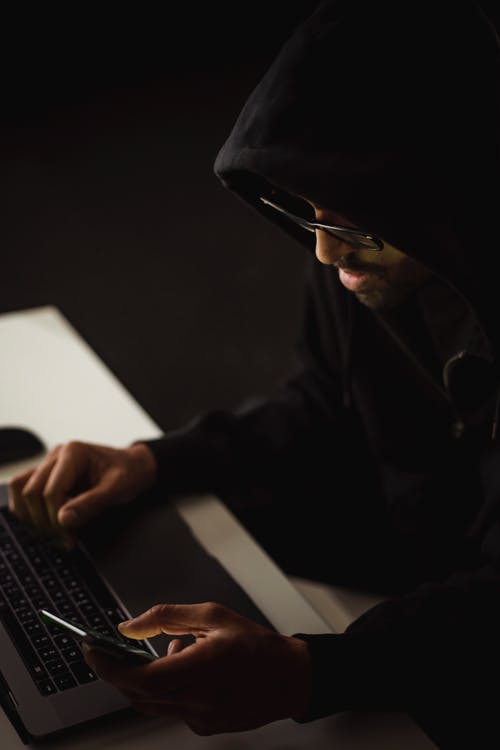From above crop focused male hacker in black hood working on netbook and mobile phone while surfing cyberspace in dark room