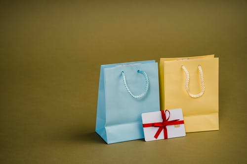 Collection of bright present paper bags with natural handles near gift card with ribbon