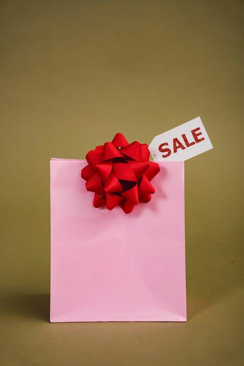 판매 태그가있는 분홍색 종이 봉지의 사진