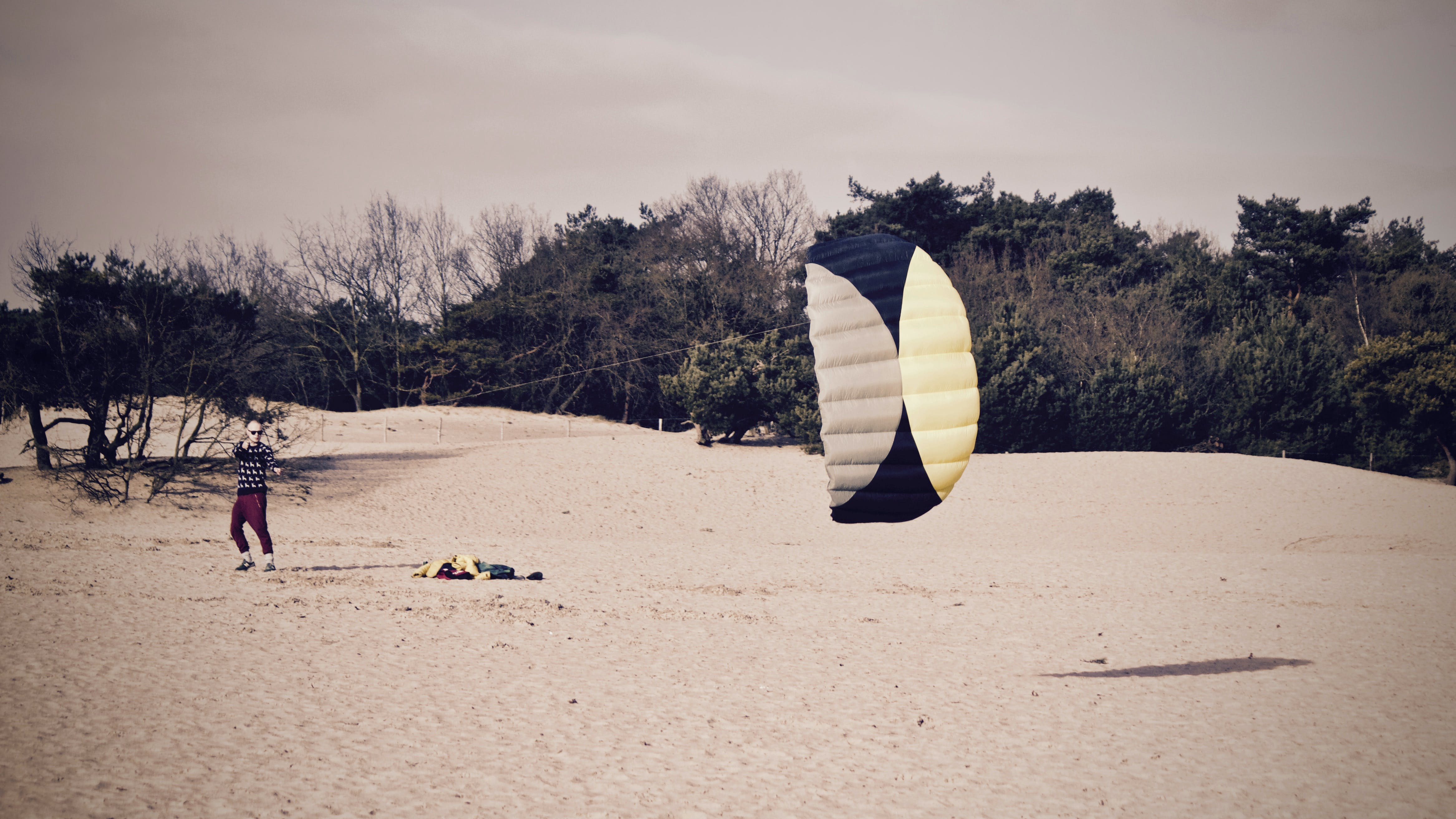 Person Holdign Black and Yellow Parachute