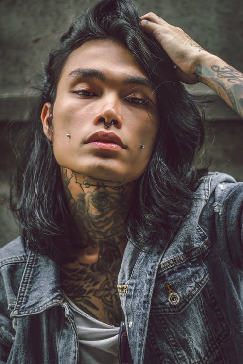 Young ethnic man with piercing on face and tattoo