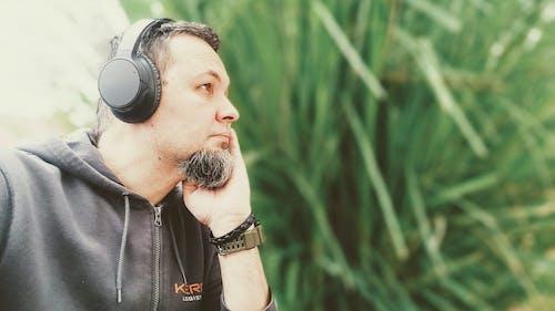 Man in Black Leather Jacket Wearing Black Headphones