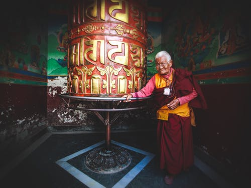 Mature monk walking around prayer wheel in temple