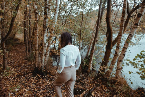 Woman in White Long Sleeve Shirt and Brown Pants Standing in Forest