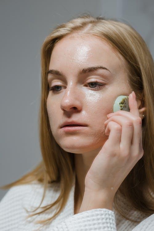 Femme En Chemise Blanche Tenant Un Ornement En Forme De Coeur Vert