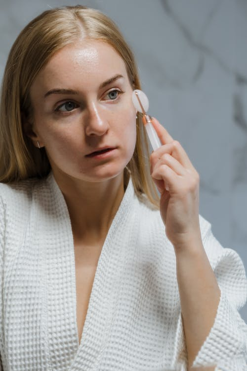 Woman in White Knit Sweater Holding Her Face