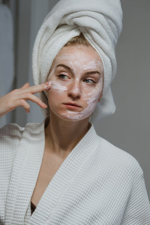 Woman in White Knit Sweater With White Face Mask