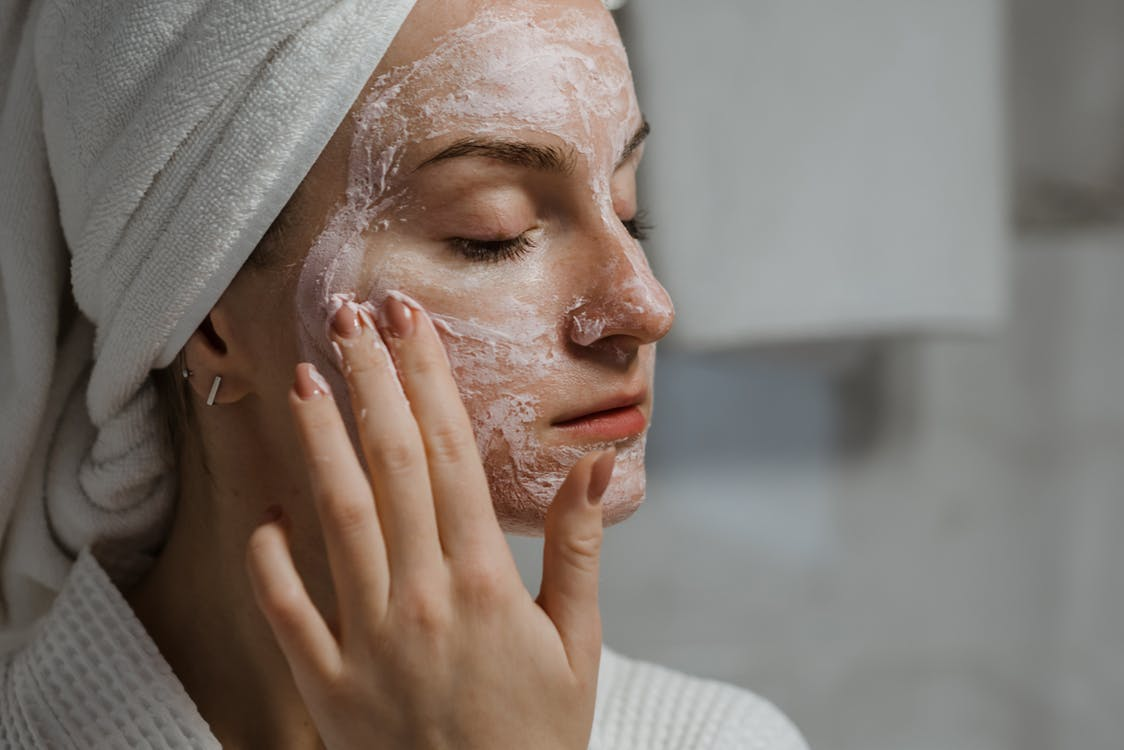 Frau Im Weißen Strickhemd, Das Ihr Gesicht Mit Weißem Textil Bedeckt