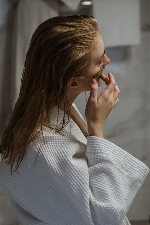 Young woman in bathrobe applying cosmetic mask on face