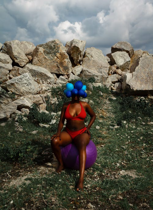 Black black woman with balloons on head in nature