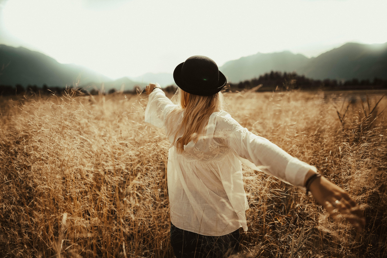 Woman Walking on Brown Grass Field