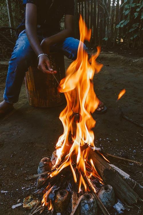 Black man sitting near bonfire in woods