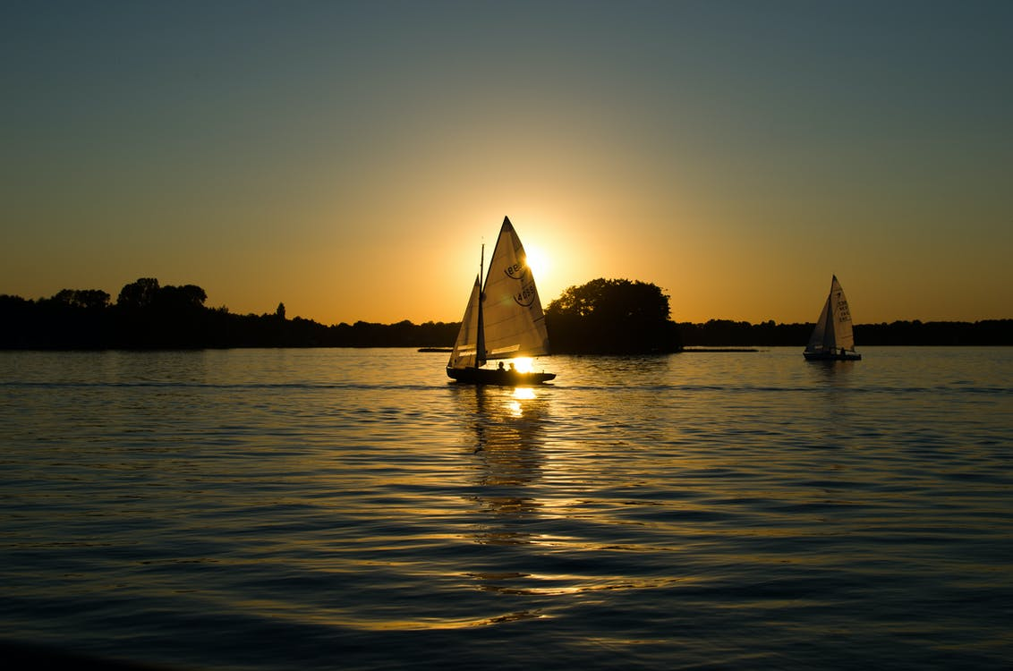 Sailboat on the Body of Water during Golden Houe