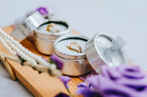 Golden wedding rings in small grey boxes on wooden stand with purple flowers