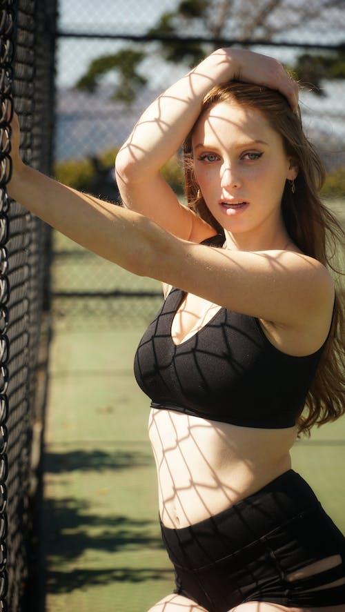 Sensual lady in sportswear near fence on sports ground