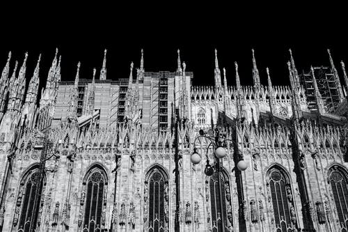 Black and white from below of aged Gothic cathedral exterior near streetlamp on street under dark sky