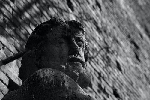 From below of aged shabby stone sculpture of man near brick building wall with shadows of trees in sunny day on city street